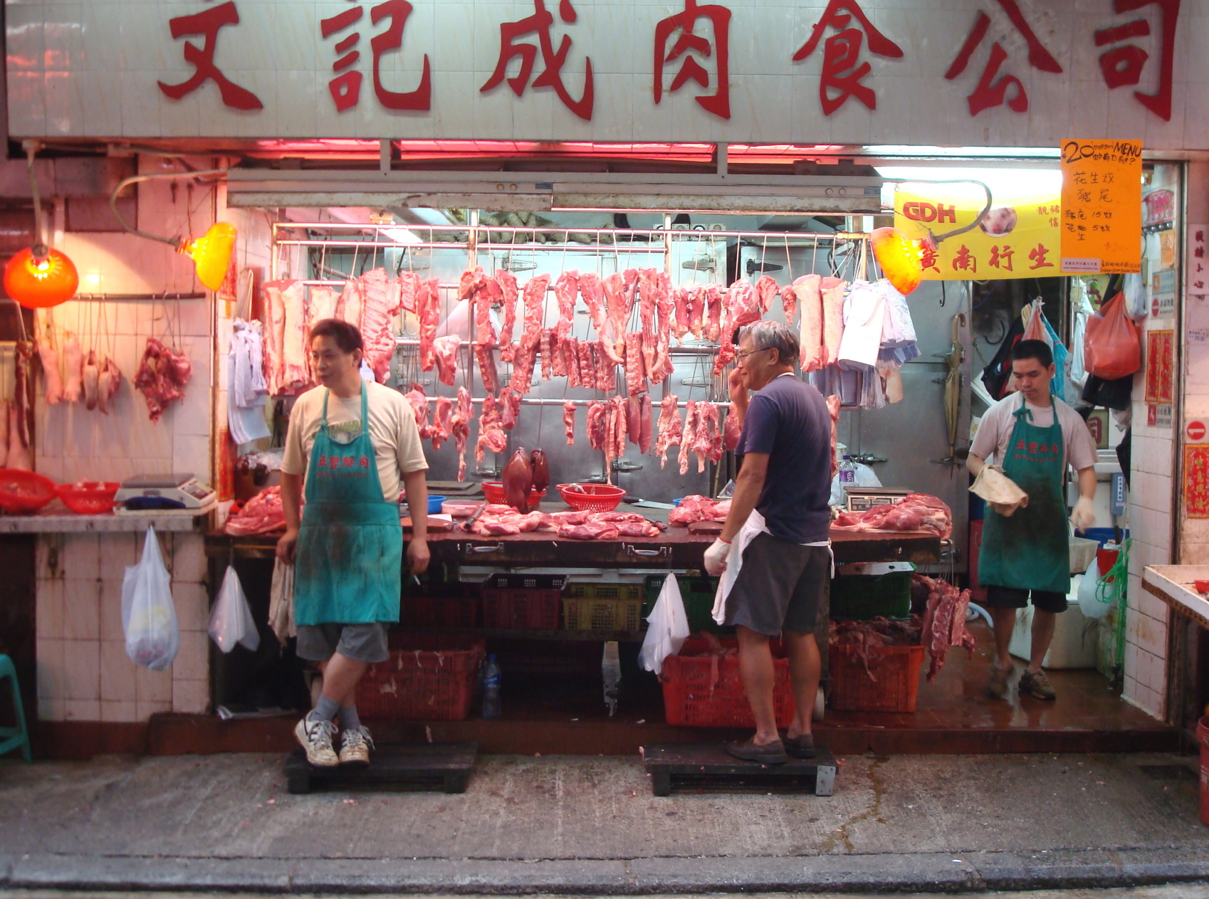 A butcher's stall with meat hanging from hooks and on the counter with two butchers standing at the stall and one exiting a door on the side