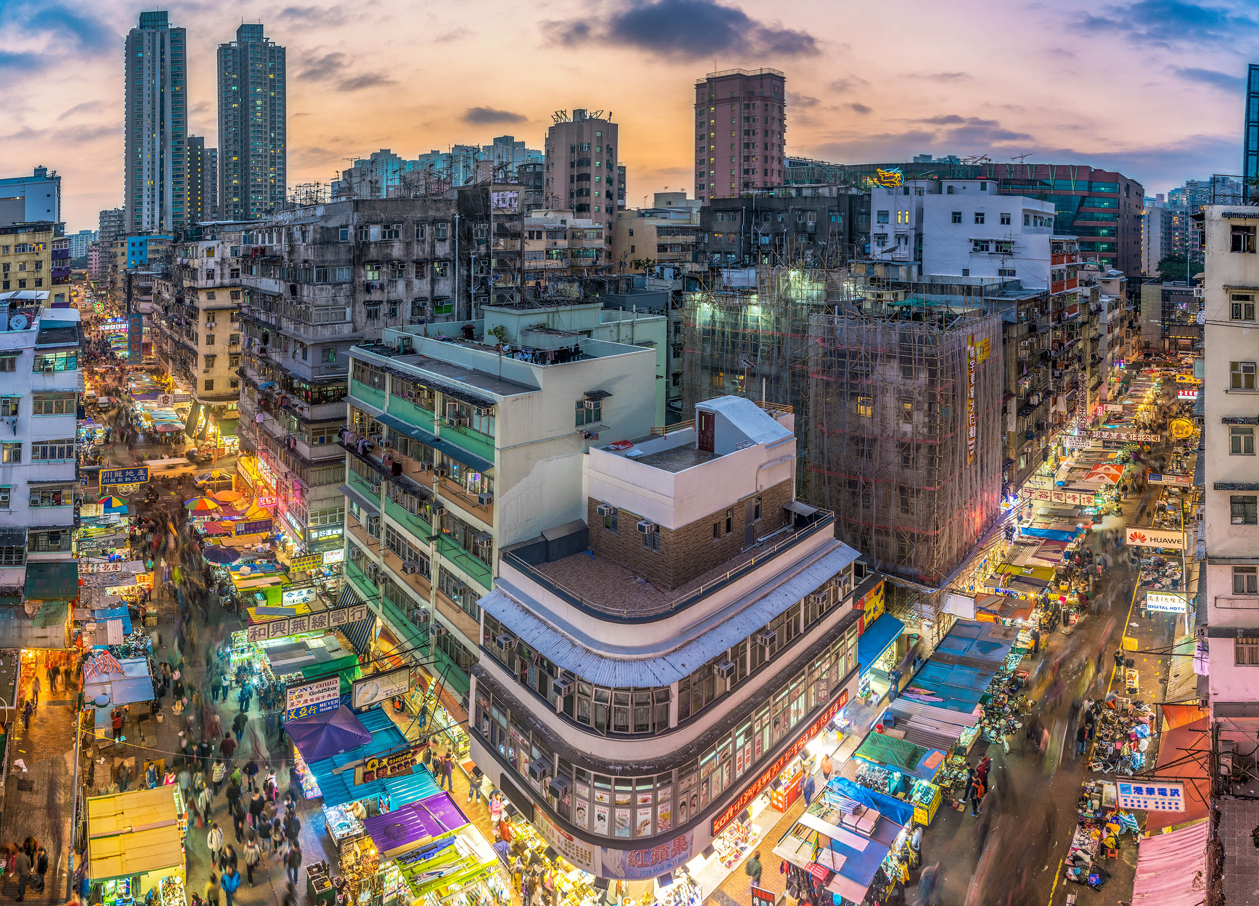 The streets of Sham Shui Po, an area situated in the northwestern part of the Kowloon Peninsula, glow with energy at dusk