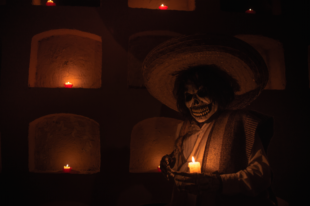 Person dressed as Santa Muerte (Death) using traditional poncho and regional hat; tombs are in the wall Photo by Misael Abad Flores