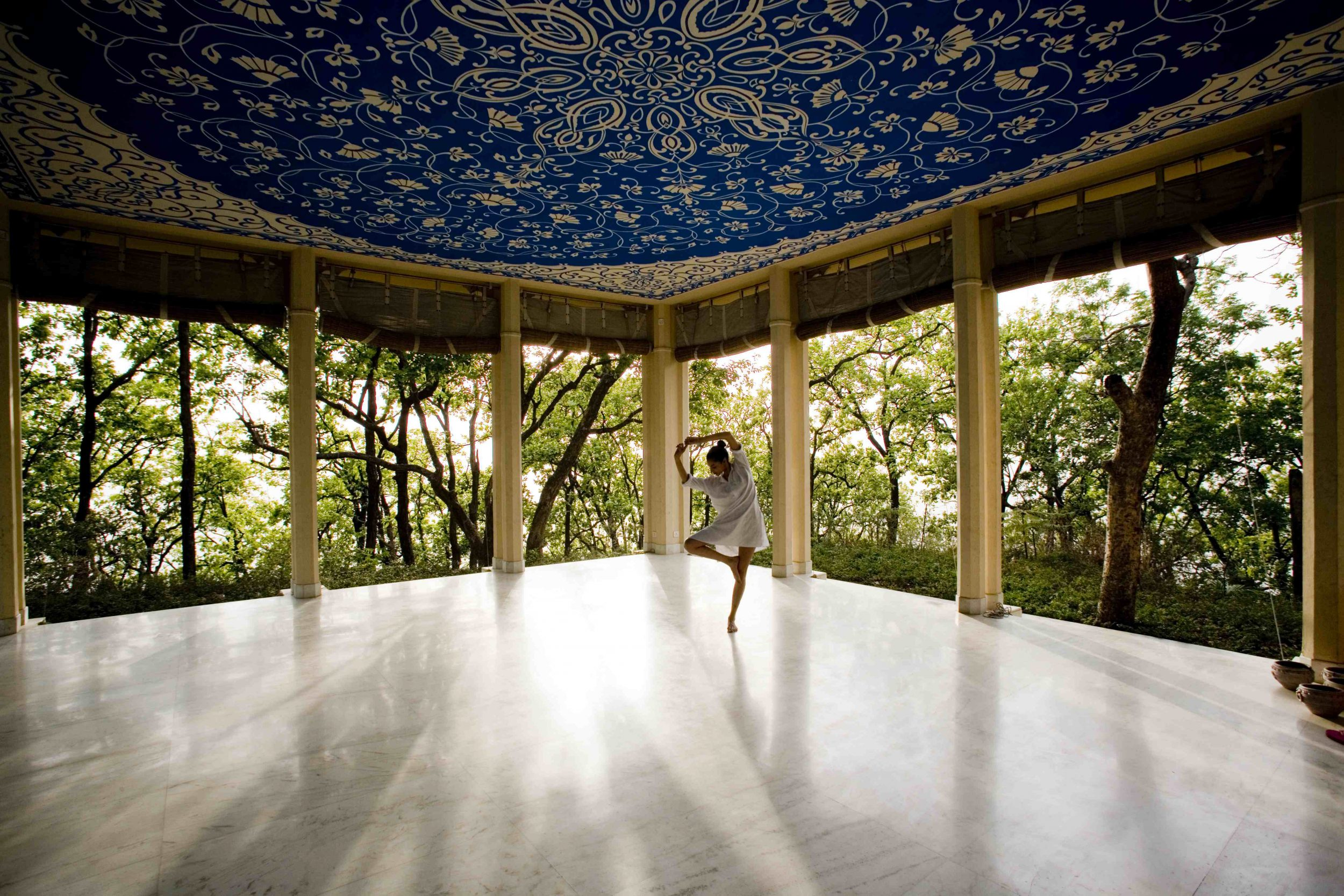 Girl in a standing yoga pose in a pillared pavilion with a blue and cream tapestry roof with the forest visible beyond, Ananda Spa, India