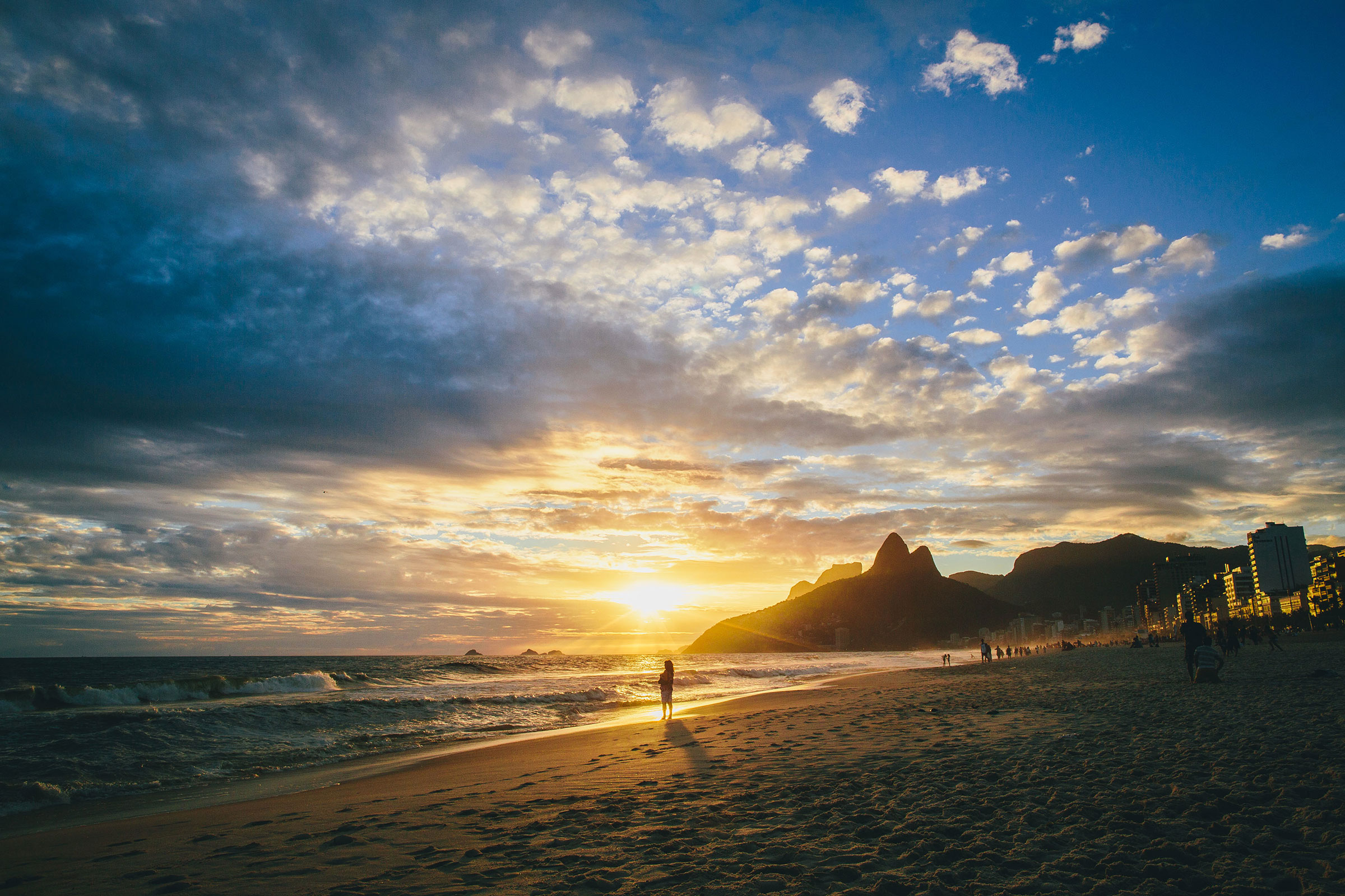 Lady sihouetted standing in the setting sun's light on Ipanema Beach, Rio De Janeiro