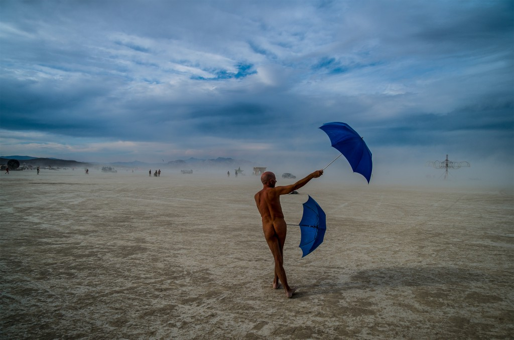 Nude man backing camera, walking through Black Rock desert waving two open blue umbrellas at the Burning Man festival