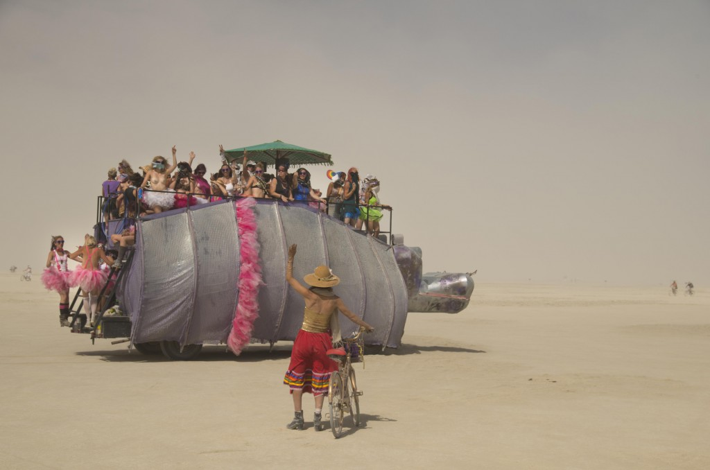 Man with a bicycle waving to a group travelling in a large metal tortoise vehicle at Burning Man, Black Rock, Nevada