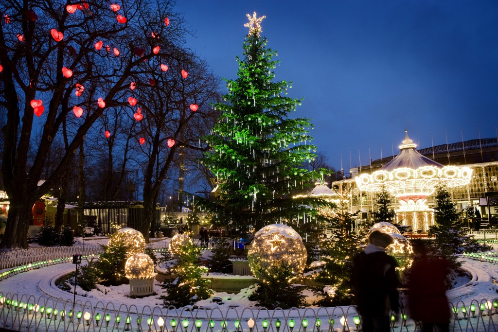 A large Christmas tree with a star atop it surrounded by lighted up glass balls in the grounds of the Tivoli Amusement Park, Denmark