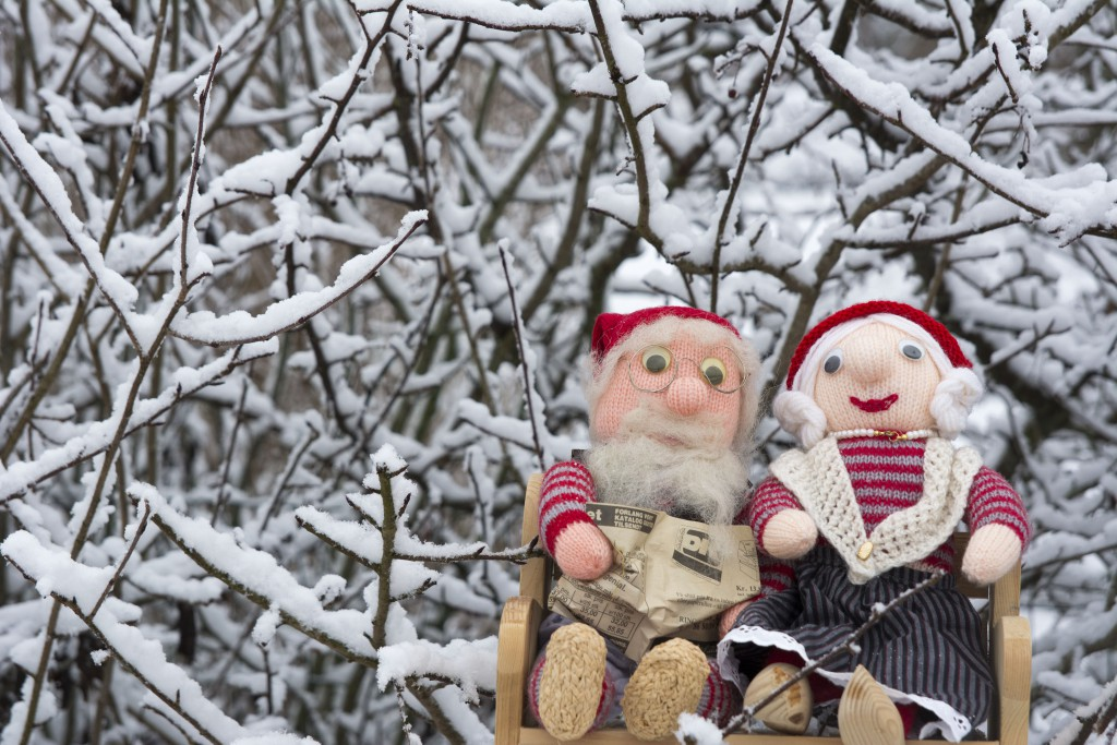 A pair of stuffed Santa's Nisser dolls sitting on a bench amongst snowy twigs