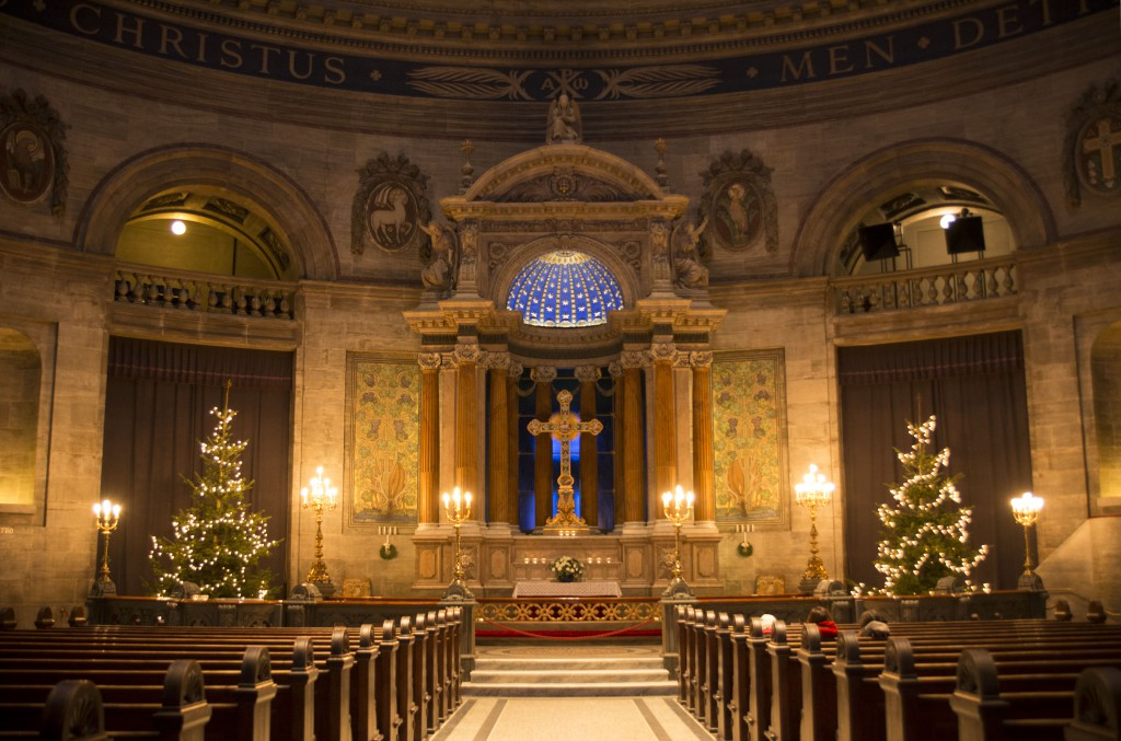The central nave and beautiful blue-domed altar with lit-up Christmas trees on either side in Frederik's Church, Copenhagen, Denmark
