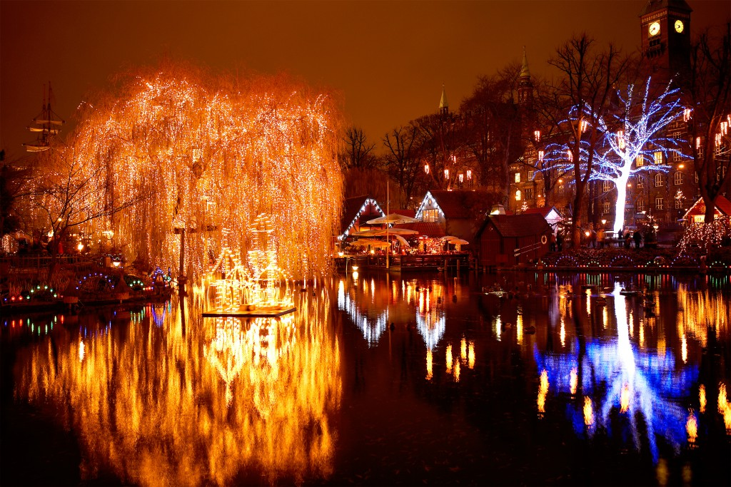 The lighted up trees and buildings of Tivoli Amusement Park reflecting into the lake, Sweden