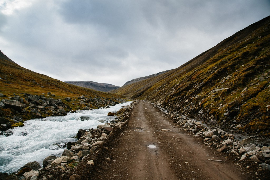 A long straight dirt road between rocky hills with ice along the entire left side of it, Iceland