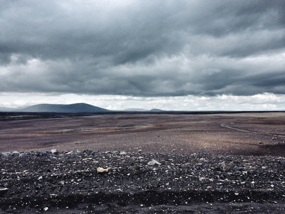 An ash desert in Iceland stretching for kilometres into the distance under a grey overcast sky