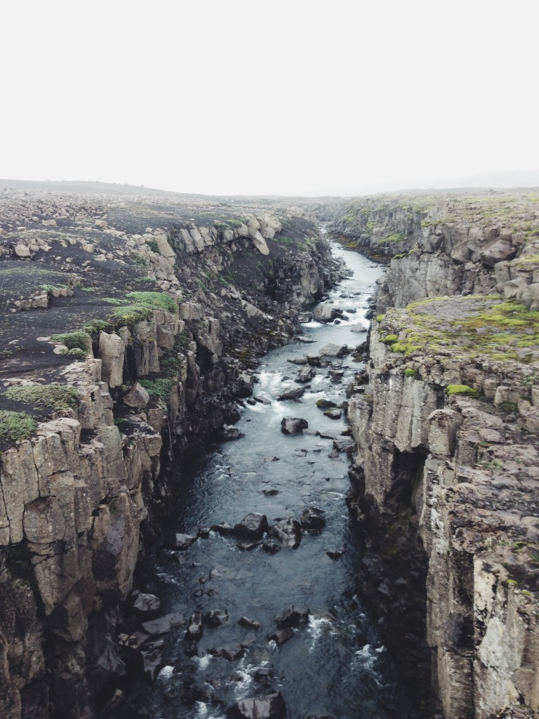 River strewn with boulders flowing through a rocky vertical-walled chasm, iceland