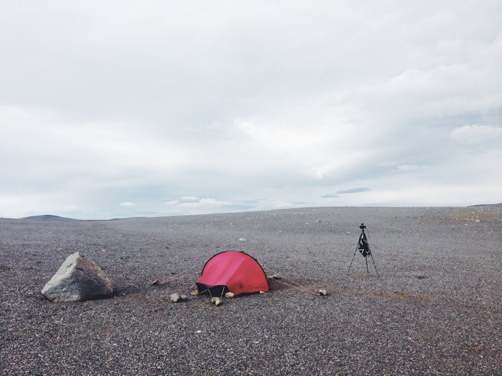 A red tent and camera tripod set up next to a solitary boulder in an otherwise empty ash desert