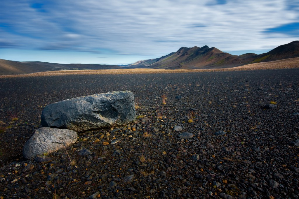 Two boulders on a mixture of stony grey, black and brown earth, lava and volcanic ash with hills in the distance, Iceland