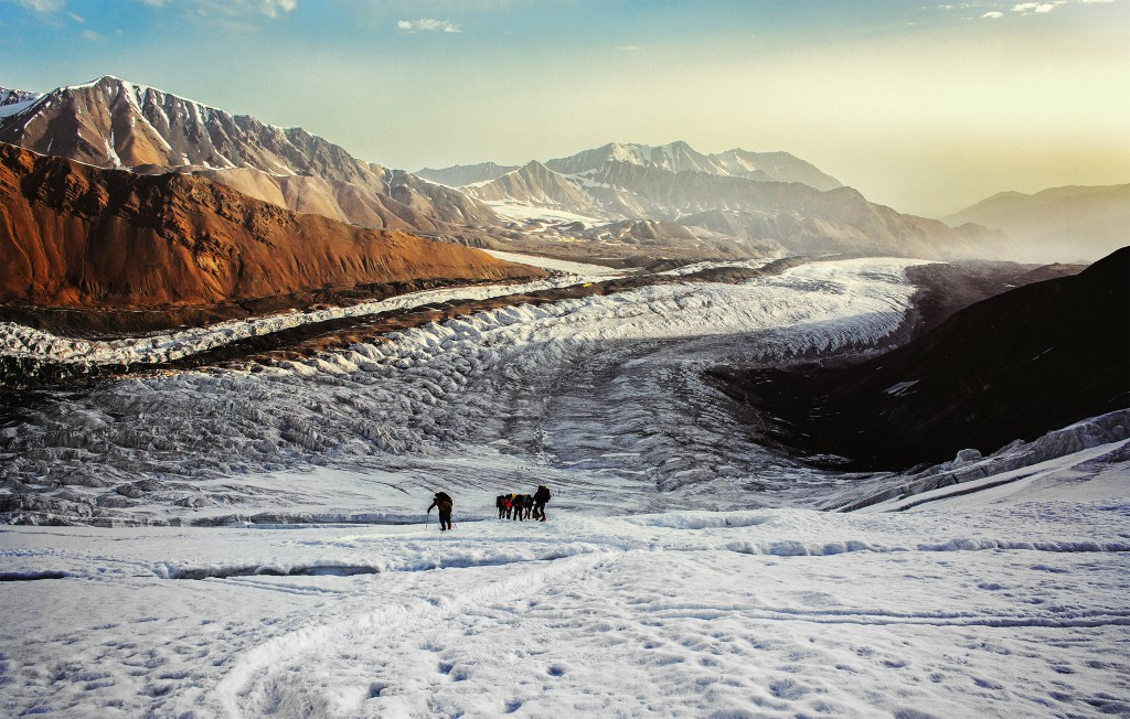 Two men and two horses trudging through the snowy landscape at sunrise near Lenin Peak
