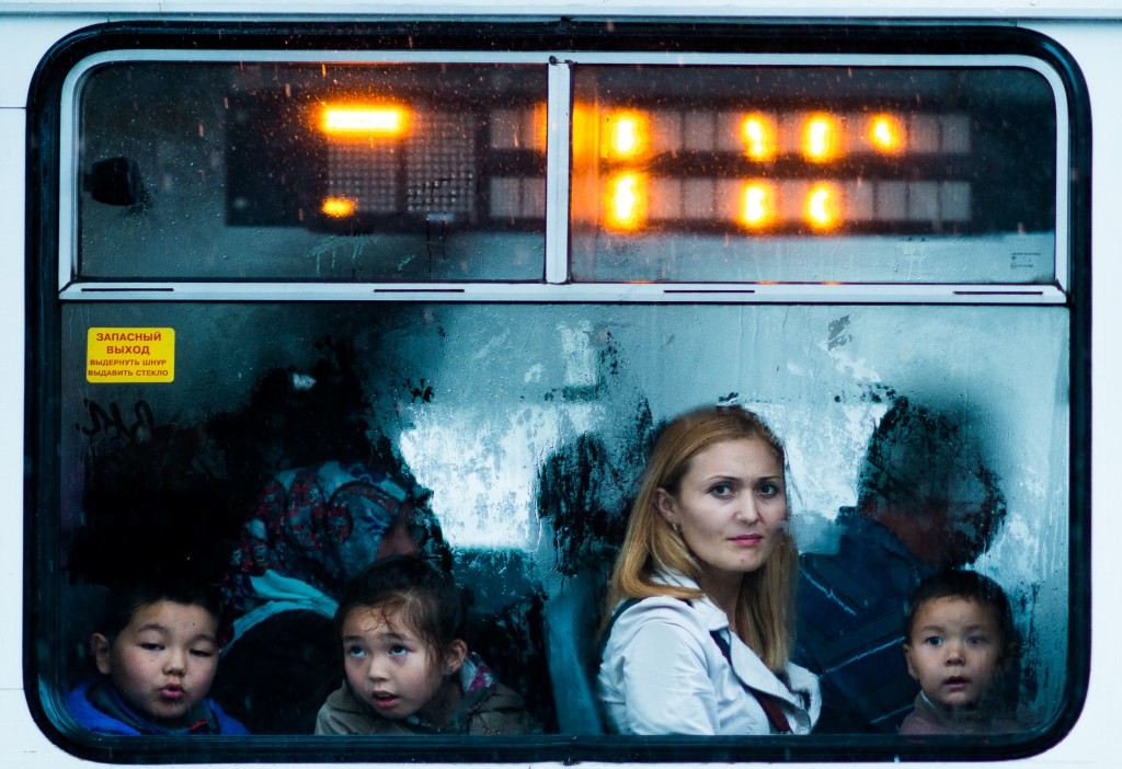 Faces of a woman and three children in a bus window in Kyrgyzstan