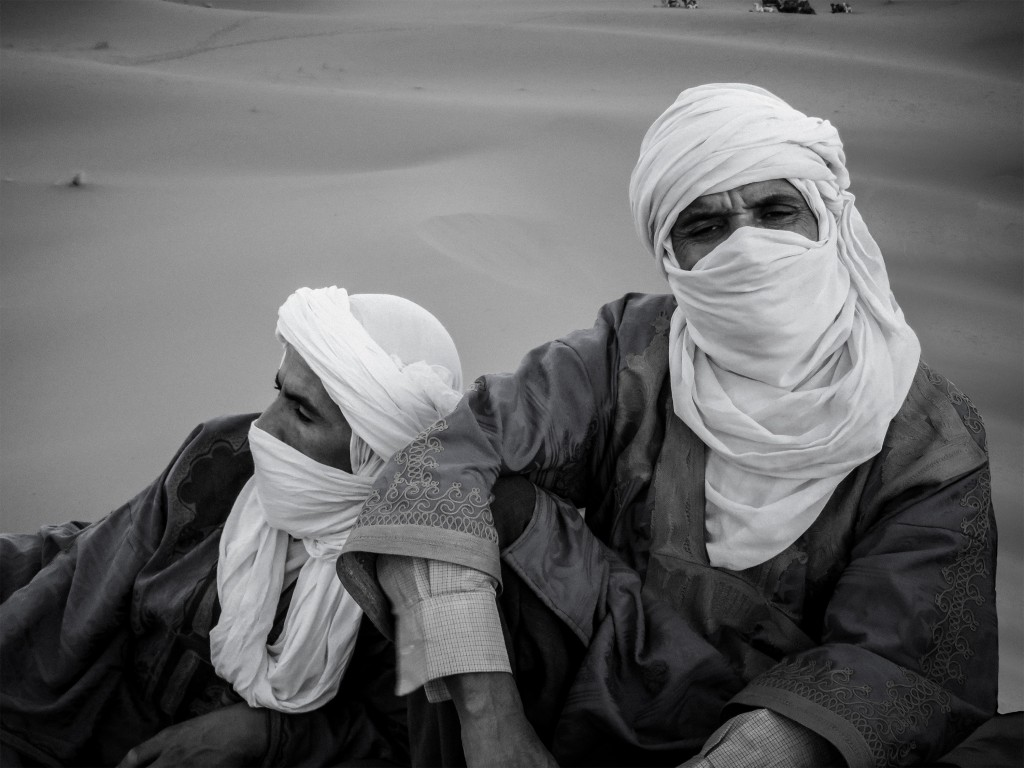 Two Berbers resting on the sand in the Merzouga Desert with their faces masked by their sheshes