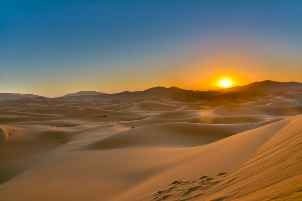 The sun setting beyond a sea of sand dunes, Merzouga Desert, Sahara