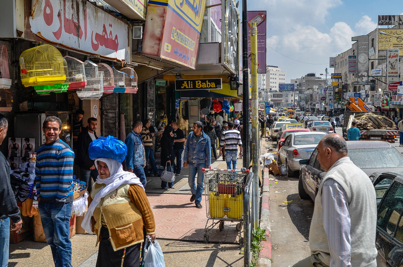 A colourful street teeming with people and cars in Ramallah, Palestine