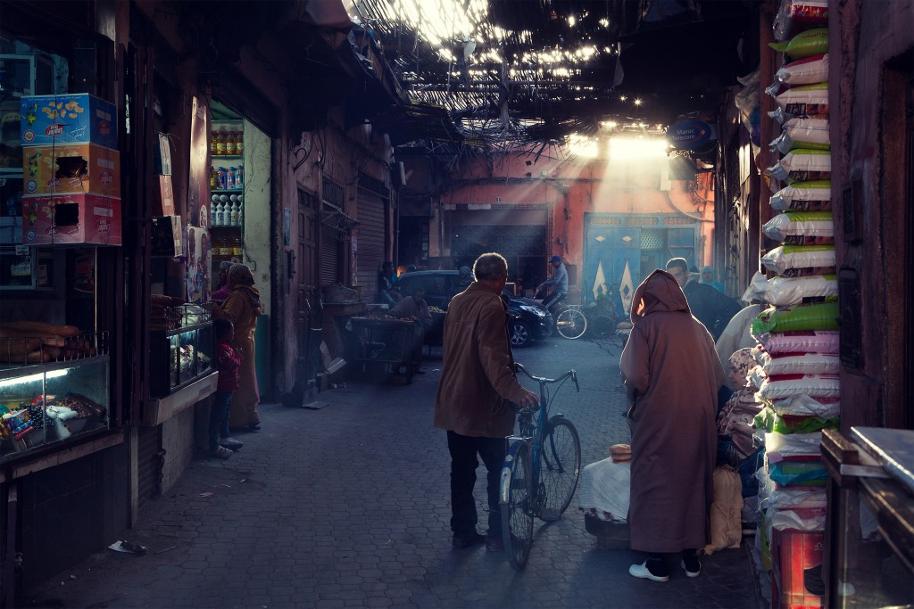 Man with cycle walking away in an alleyway in Marrakesh