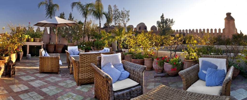 Seating areas and and potted plants on the rooftop terraces of Dar Les Cigognes, Marrakesh, Morocco