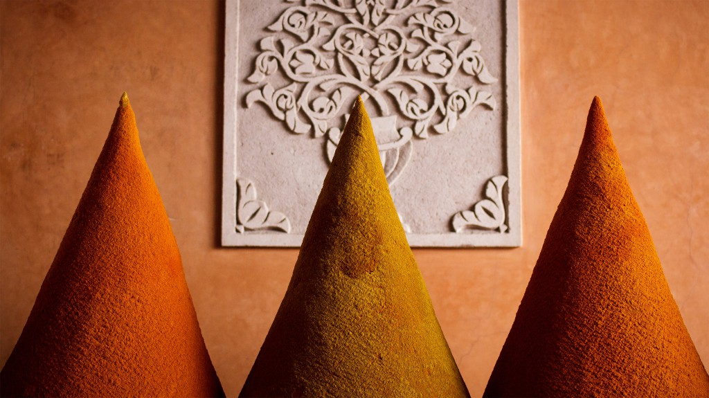 Spice-powder in three conical piles against a bas relief wall, Marrakech, Morocco
