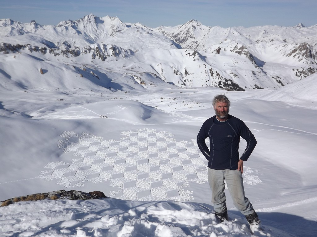 Simon Beck standing by one of his large geometrical designs in the snow (an array of squares in a snowflake pattern) with snowy peaks stretching into the distance