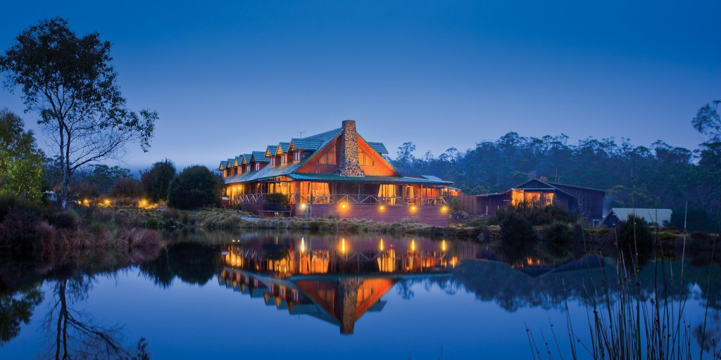 A lighted up Cradle Mountain Lodge reflecting into the lake at dusk — Tasmania, Australia