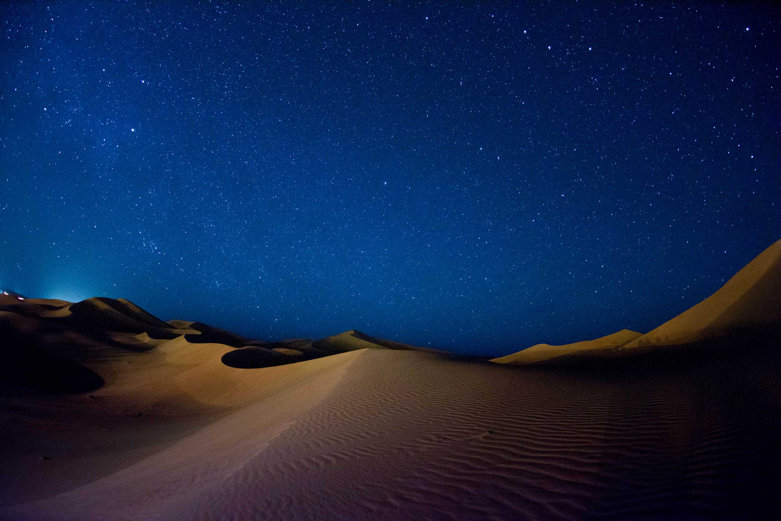 A view of the dunes and a starry, deep blue sky at the Merzouga Desert, Sahara