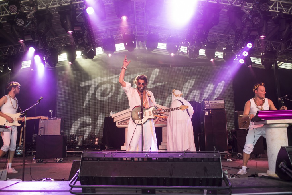 A rock band dressed in white performing on a purple lighted stage, Golden Plains, Australia