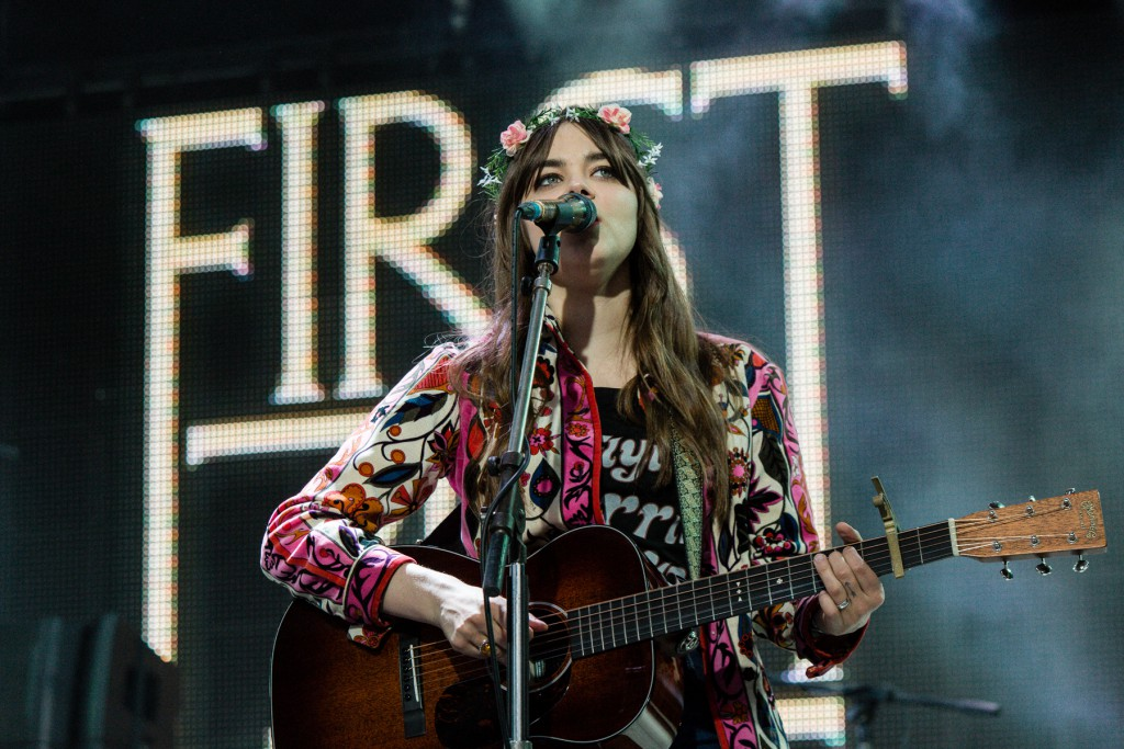 Girl wit a floral headband playing the guitar and singing on stage, Golden Plains, Australia