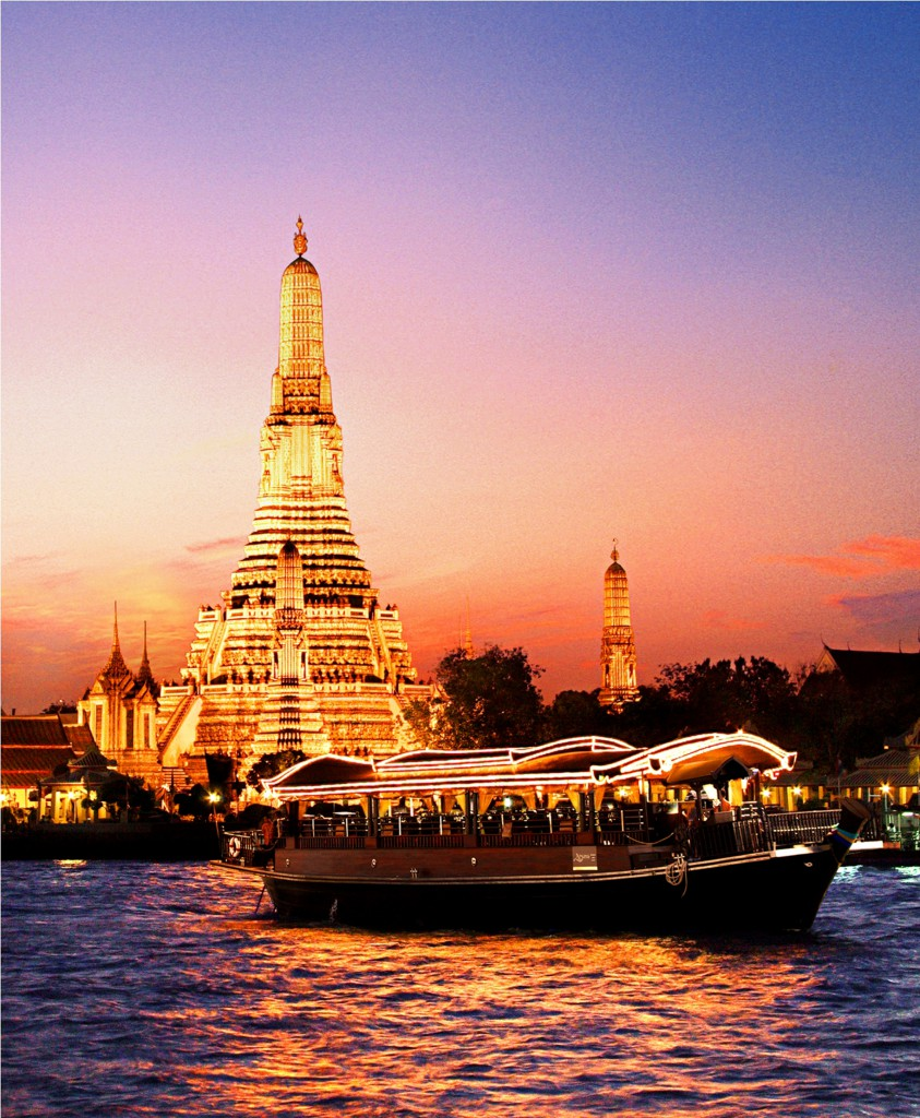 A view of Wat Arun from the Chao Phraya, Bangkok, lighted up at night with the Apsara dinner cruiser in the foreground
