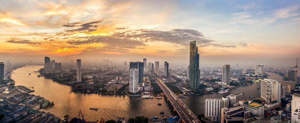 Panoramic view of the Chao Phraya River and Bangkok city at sunset with hues of yellow and orange in the clouds and sky