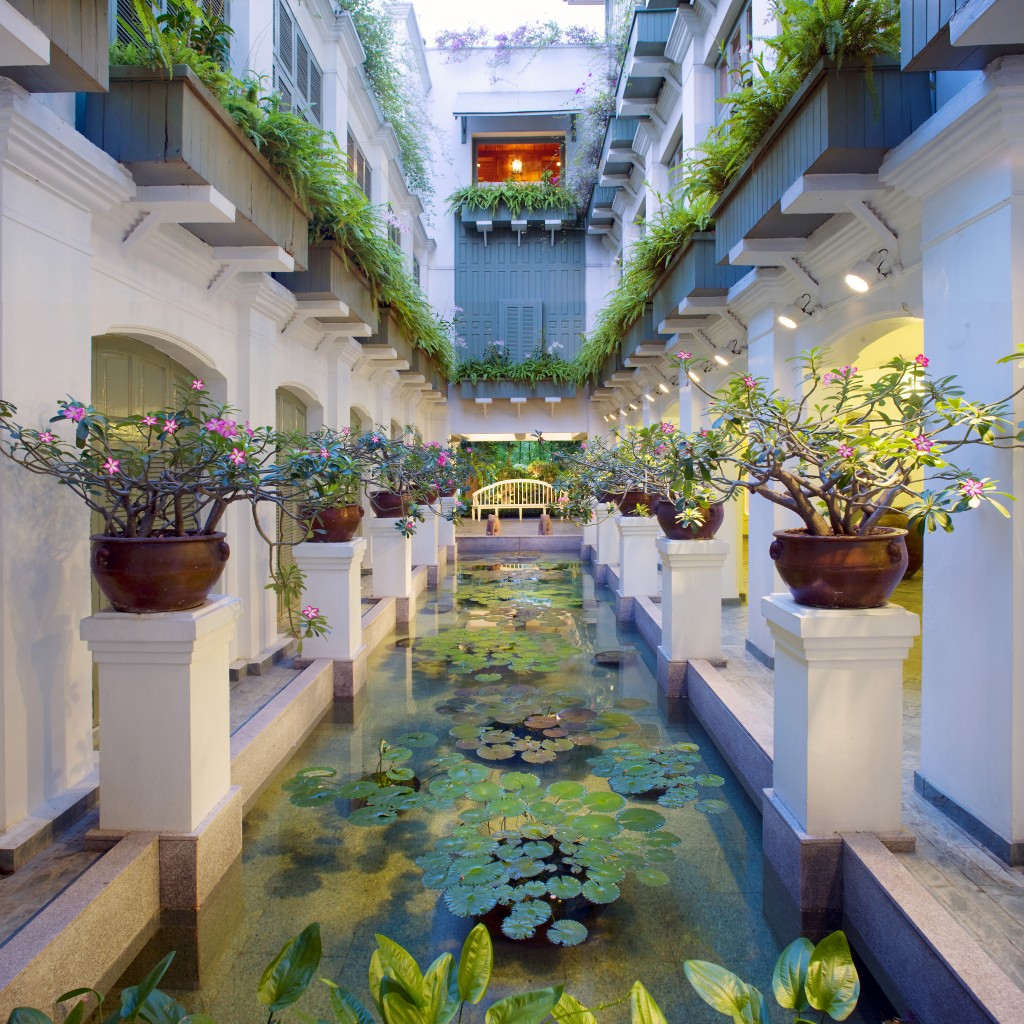 A long tranquil water feature filled with water lily plants in the atrium of The Oriental Hotel, Bangkok.