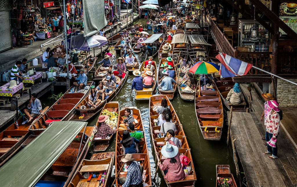 A khlong filled cheek by jowl with boats carrying locals and their produce in Bangkok, Thailand