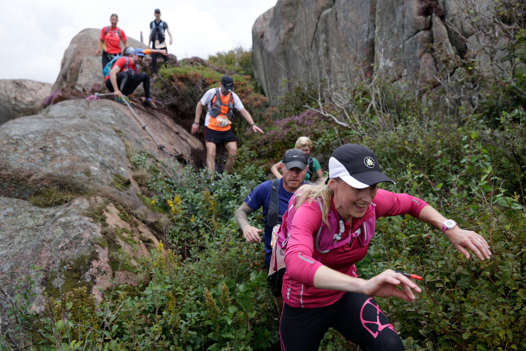 Group of runners sliding down a rock with rope ties and running through bush between the rocks on the Icebug Xperience marathon