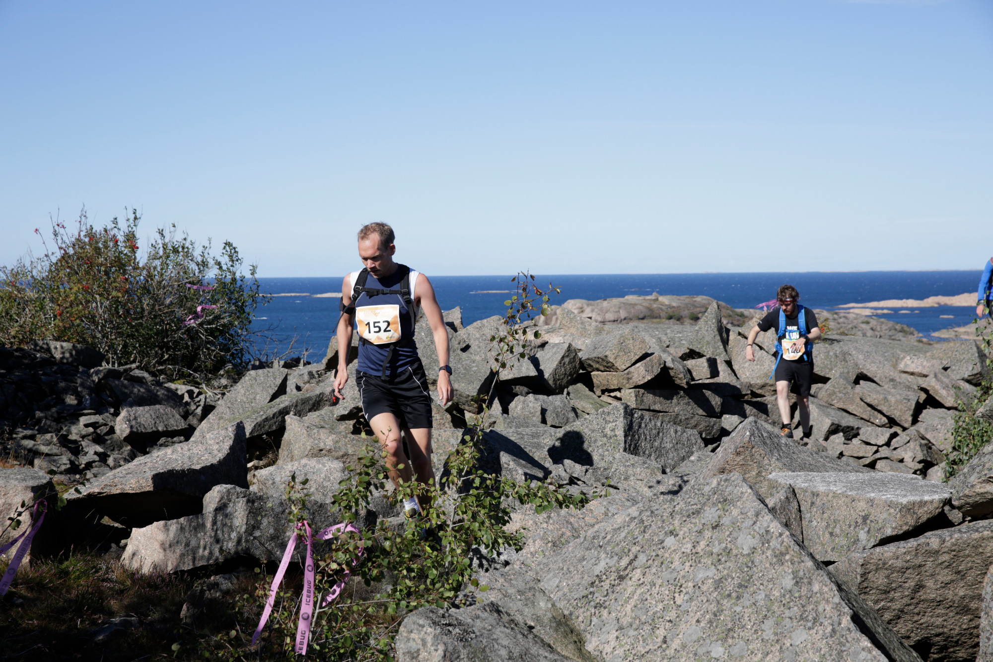 Two runners wending their way through rock with the sea in the background on the Icebug Xperience marathon