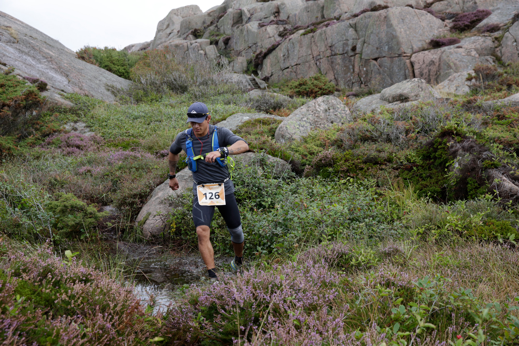 Man running through vegetation growing between rocks and boulders on the Icebug Xperience marathon