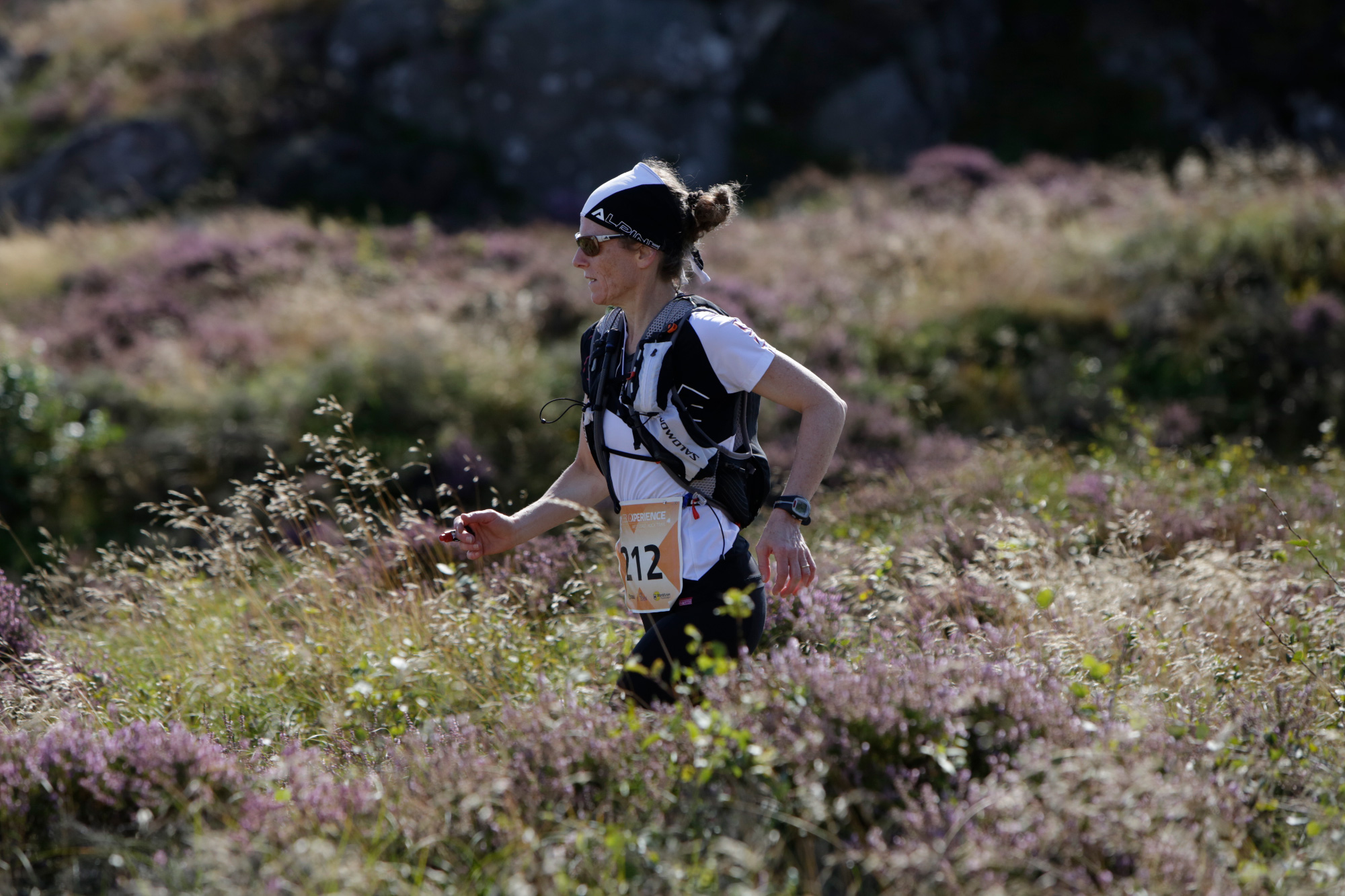 Woman running through waist high vegetation on the Icebug Xperience marathon