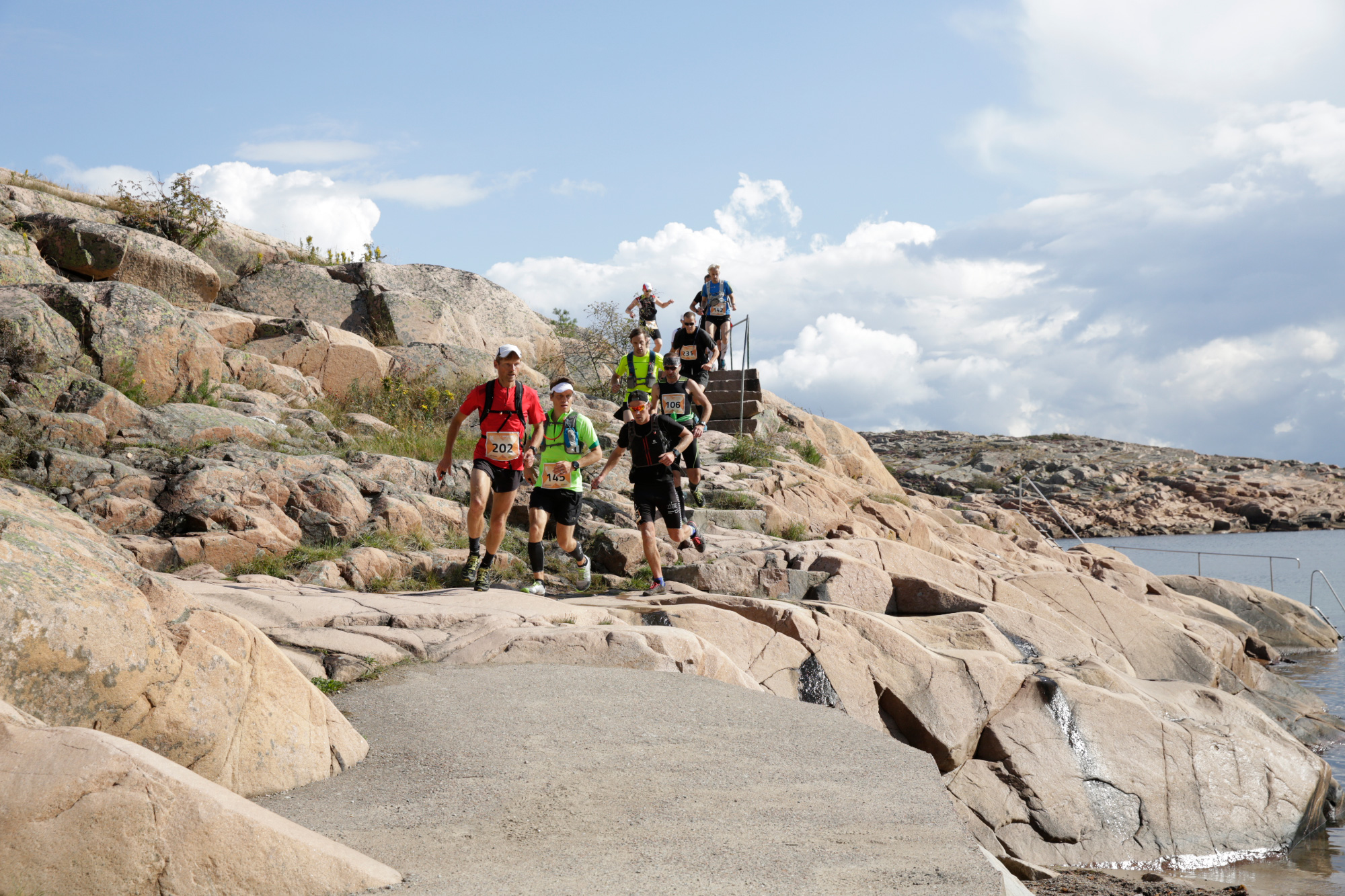 Group of runners descending steps and rocks by the sea on the Icebug Xperience