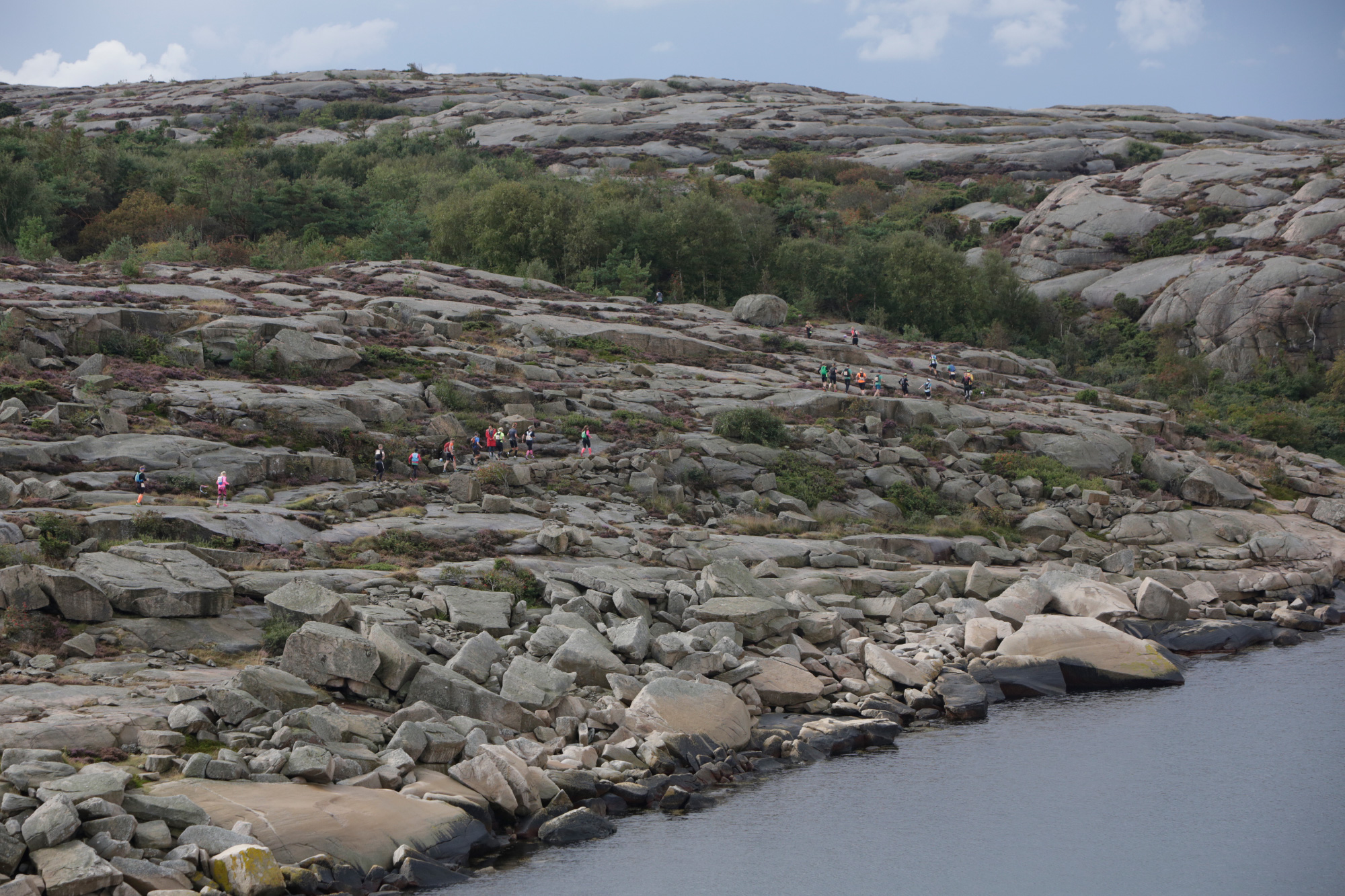 Long shot of runners running through very rocky landscape along the sea on the Icebug Xperience marathon