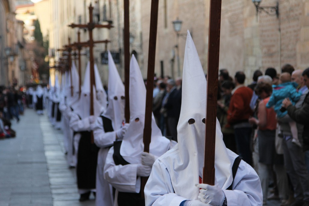 A line of white-hooded masked men carrying crosses