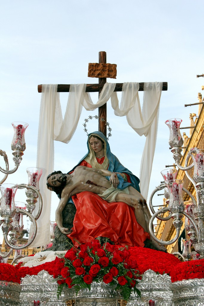 Statue of virgin Mary holding a dead Christ in her lap on a float at Semana Santa