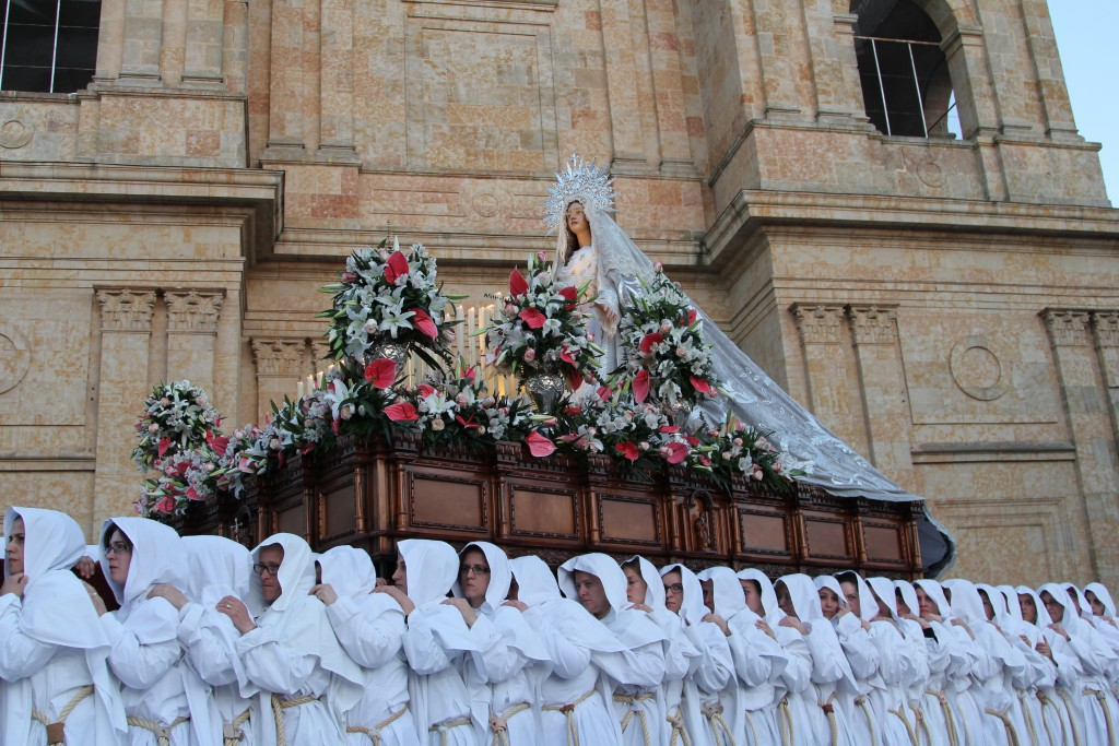 Large group in white robes carrying the Virgin Mary on a decorated platform
