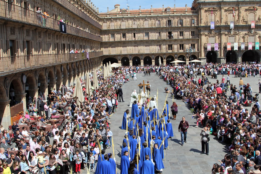 Men in blue robes walking through the crowd, Semana Santa