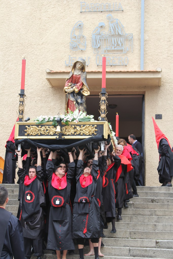 Black and red robed group of men carrying a statue of Virgin Mary held aloft down church steps