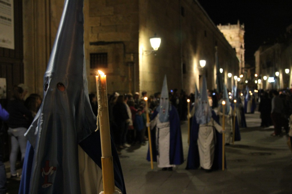 Robed figures in procession at nght