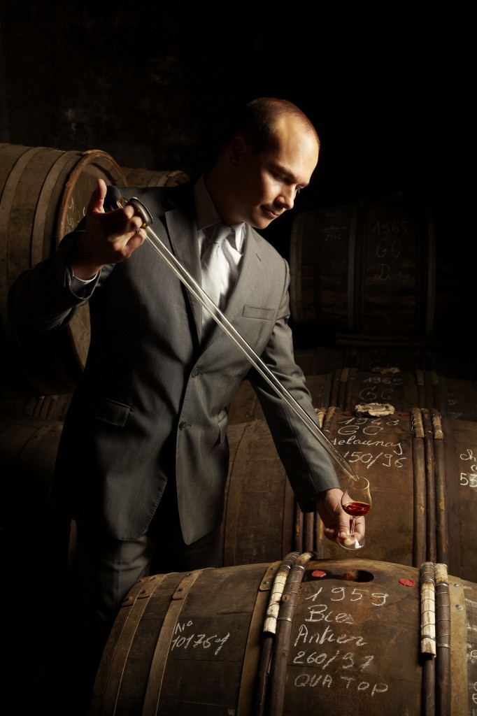 Benoit Fil, Martell Cellar Master drawing wine from a cask into a wine glass with a pipette in Cognac, France