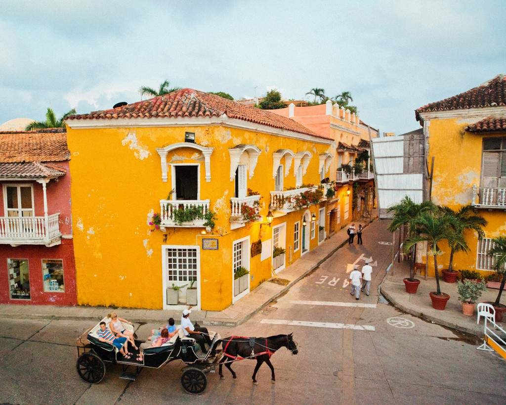 A family strolls by in a horse-drawn carriage outside La Vitrola, one of the iconic restaurants along the outside walls. of Cartagena, Colombia.