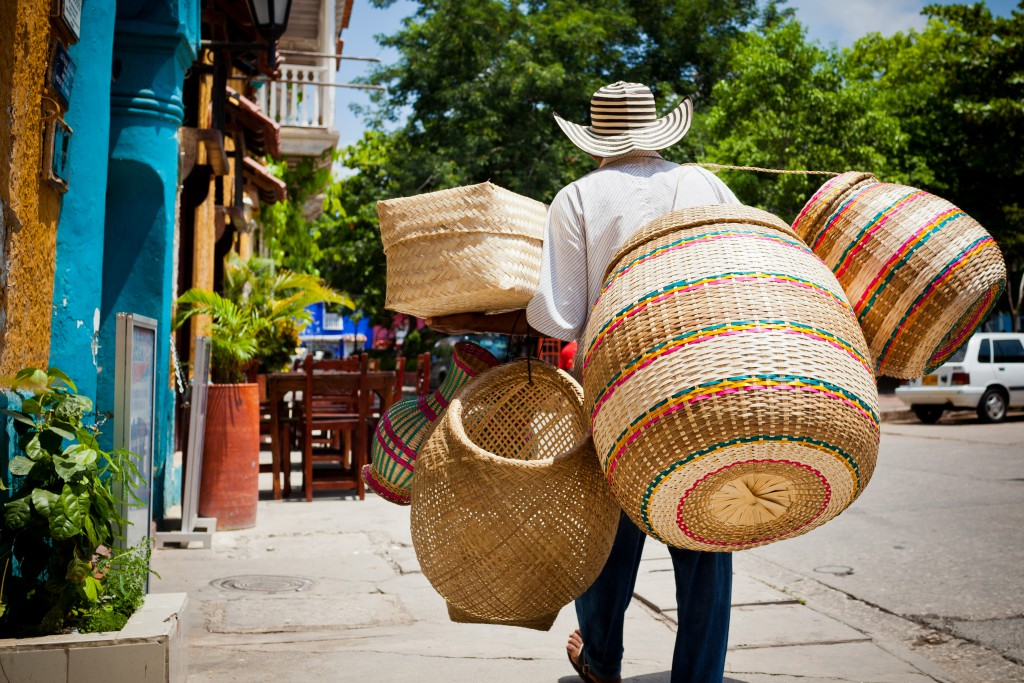 A basket vendor strolls the streets within the walled city of Cartagena, Colombia in the sweltering South American heat.