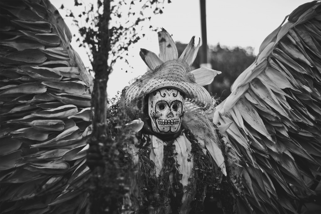 Reveller celebrating the Day of the Dead in Mexico dressed in a skull mask and wings