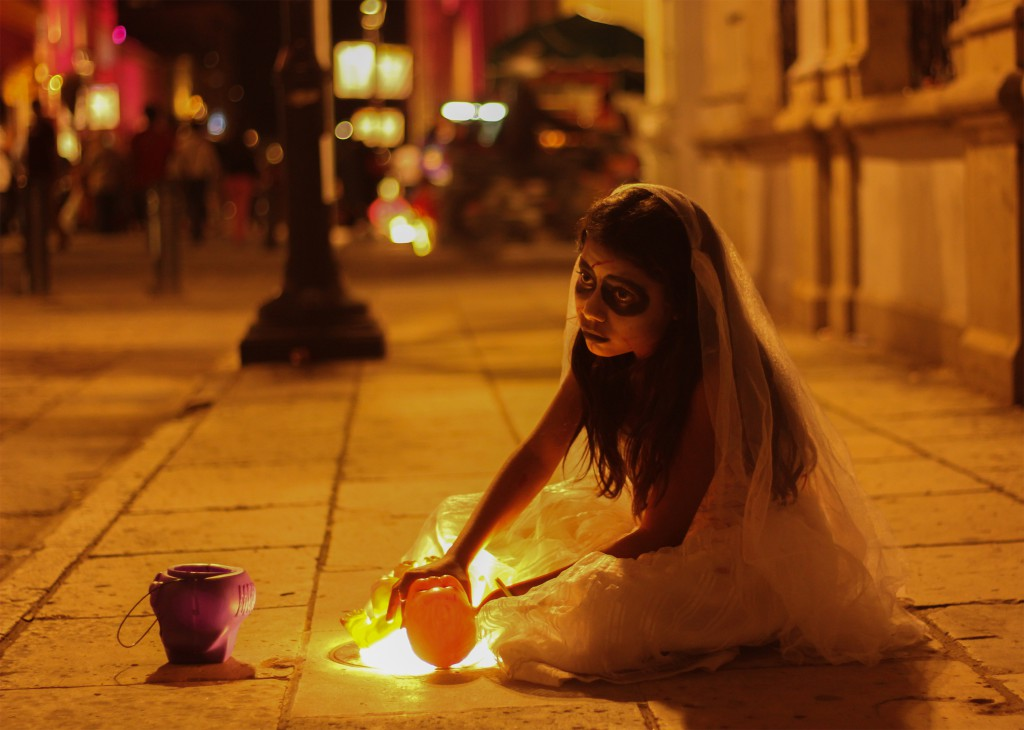 Woman sitting on the pavement in white robes in Mexico for Day of the Dead